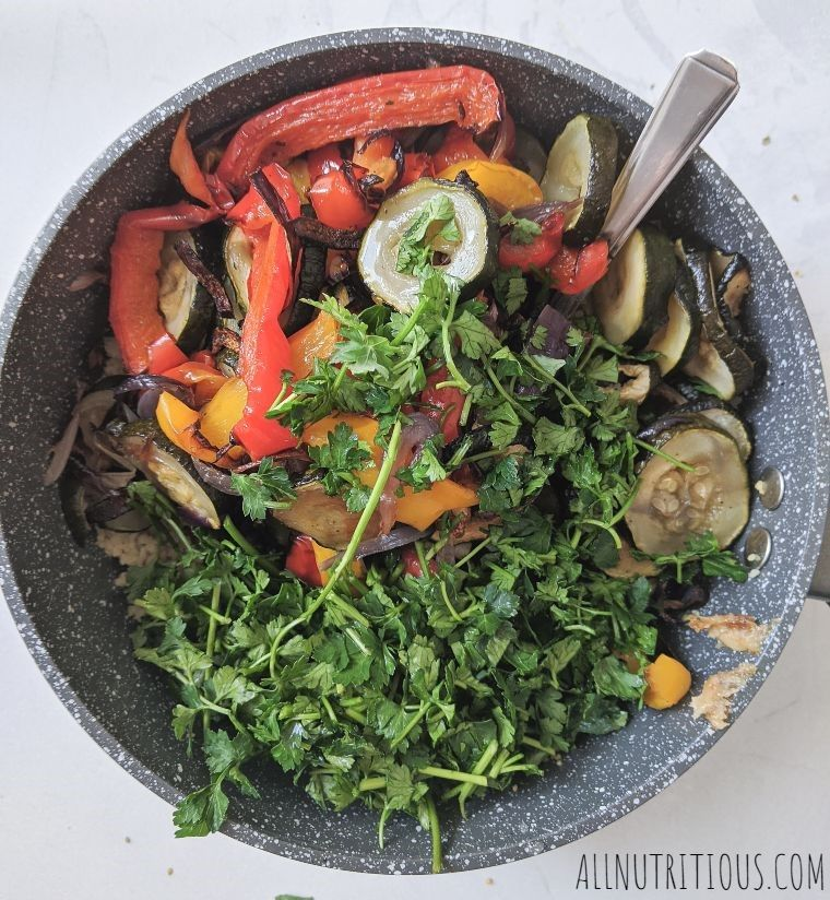 roasted vegetables with couscous and herbs in a saucepan