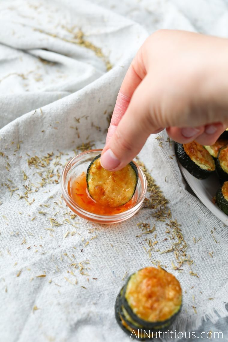 dipping zucchini bites in sauce