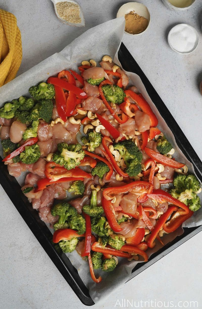 sheet pan with uncooked chicken and veggies