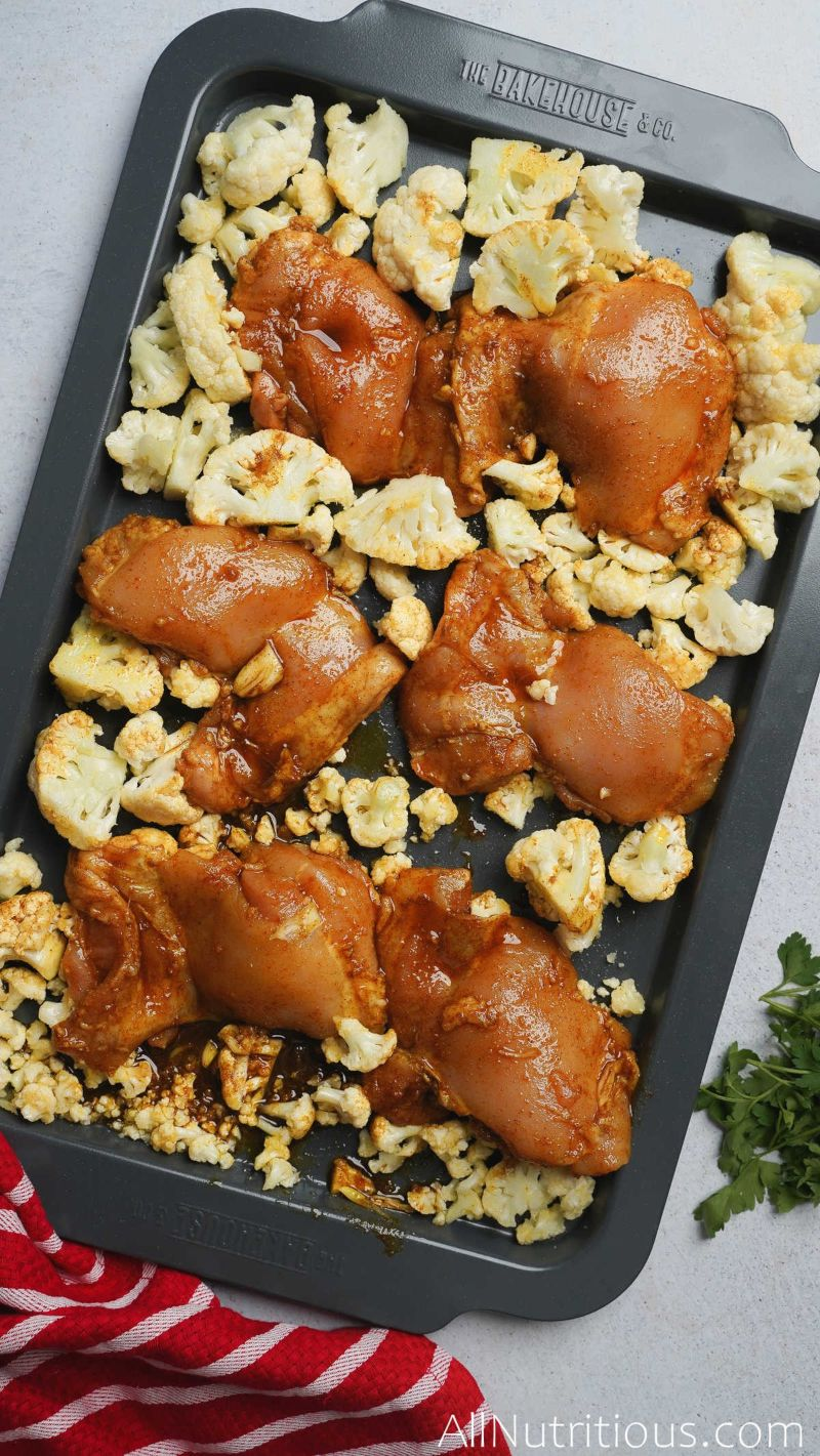 sheet pan with marinated chicken thighs and cauliflower