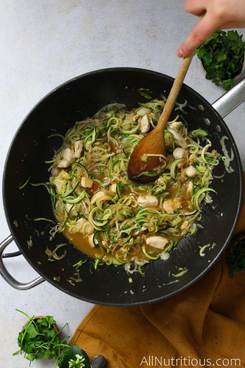 adding sauce to zucchini chicken pasta