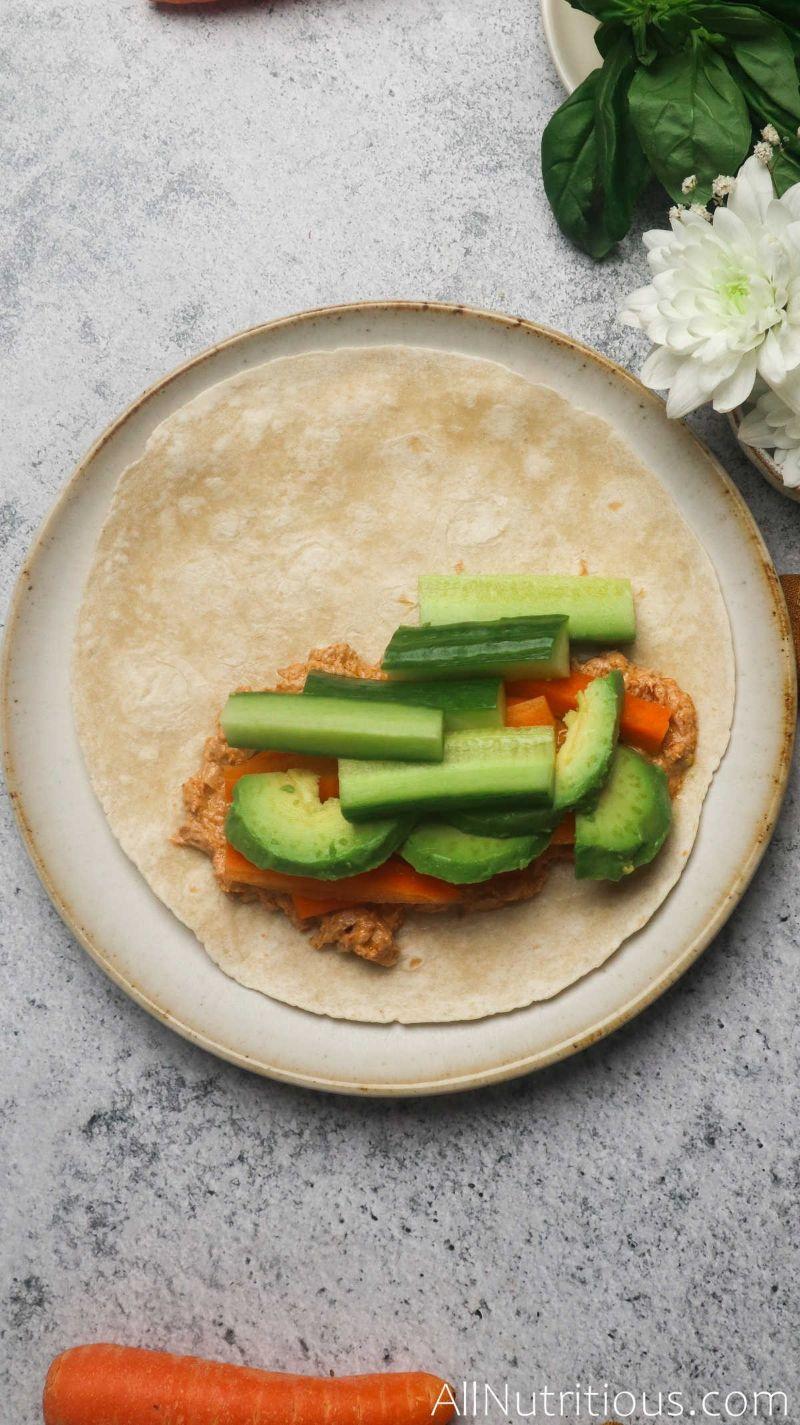 adding veggies to tortilla