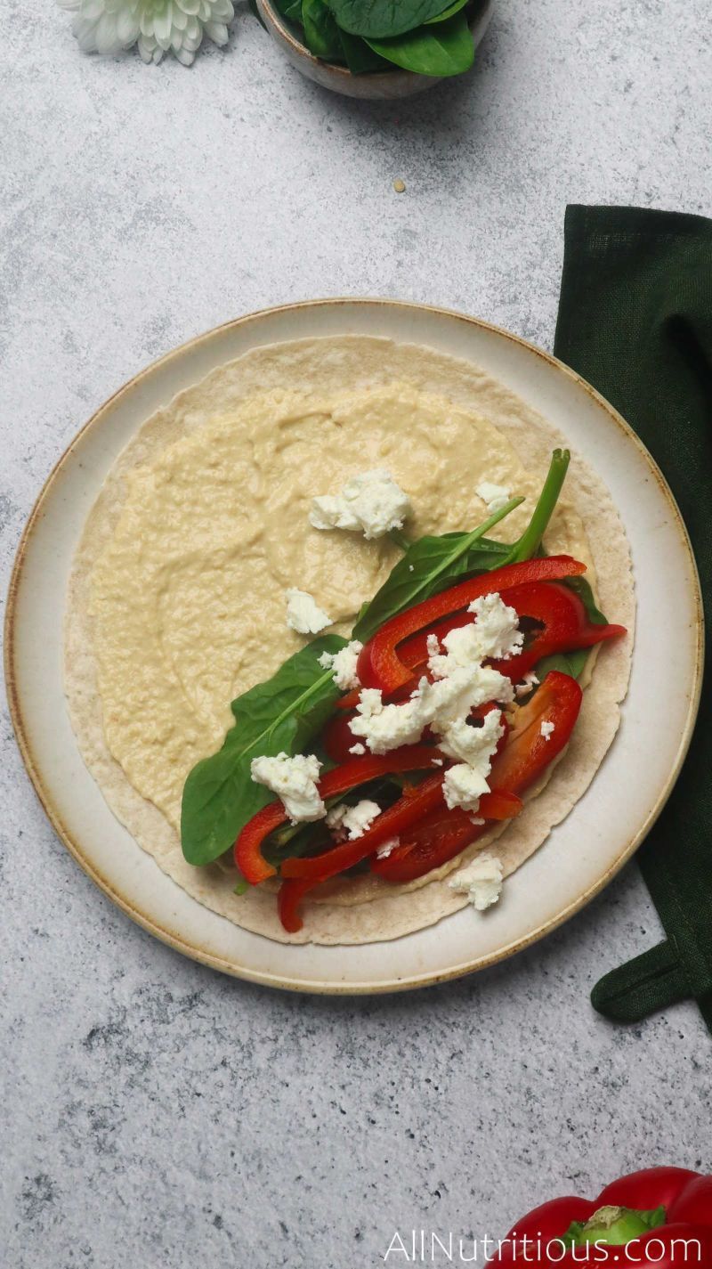 adding veggies and feta to tortilla