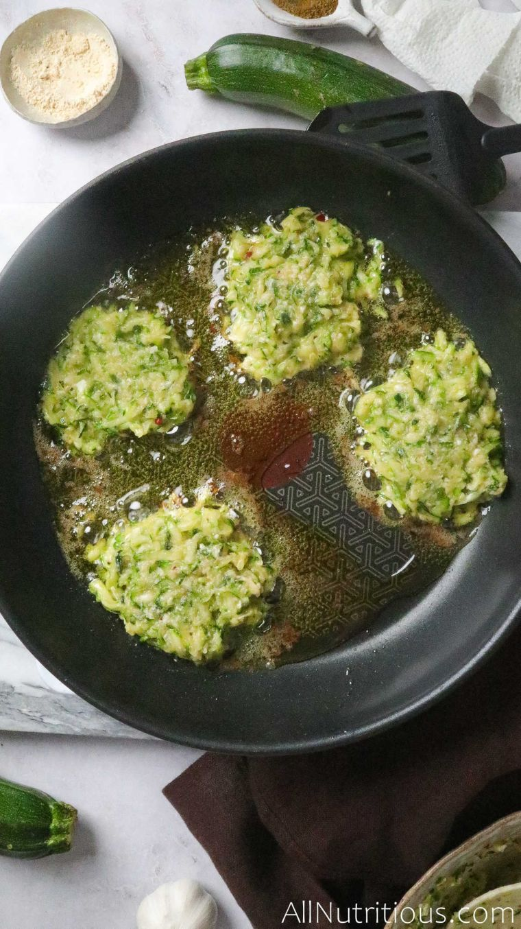 zucchini fritters in pan with oil
