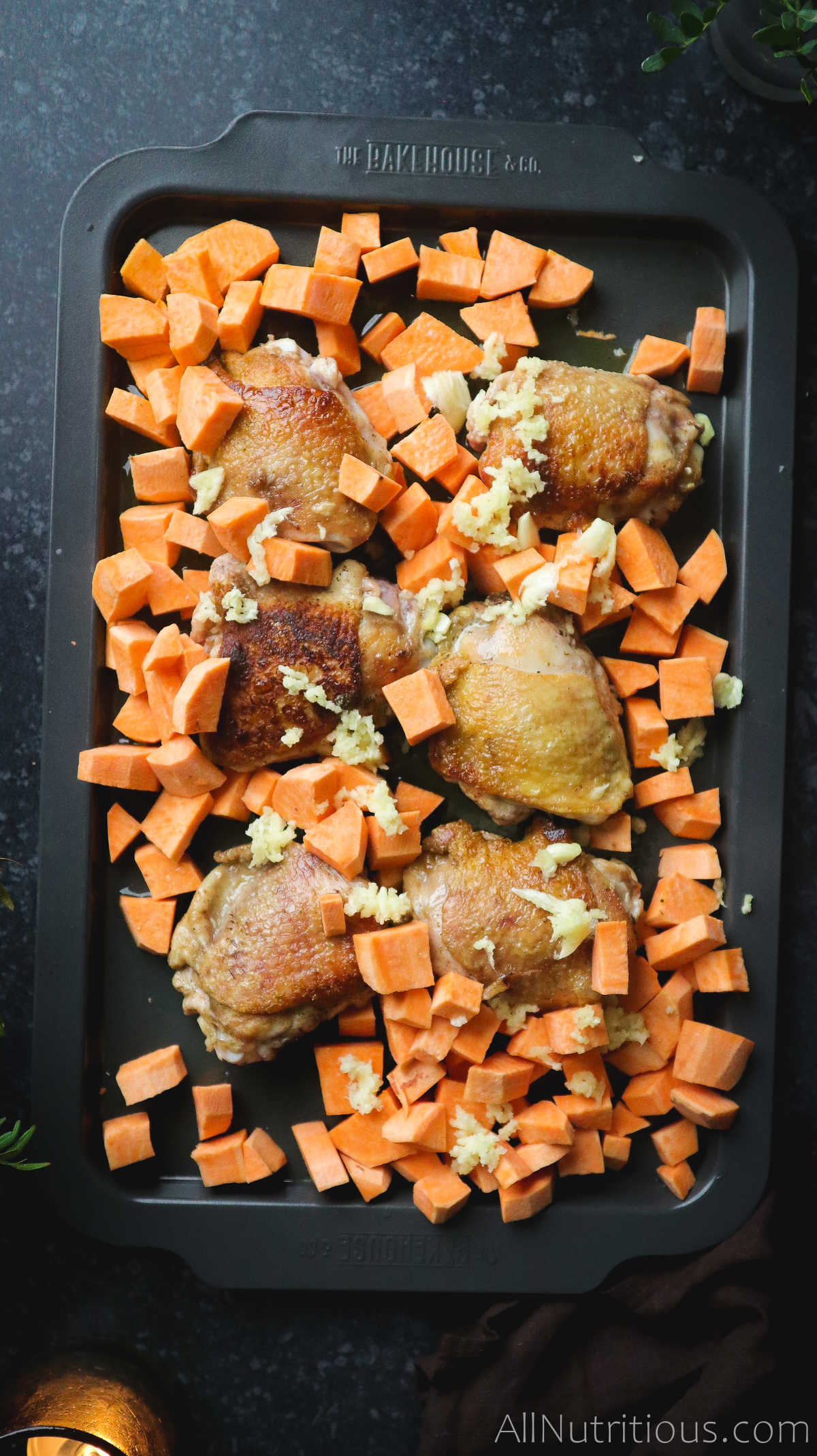 chicken thighs and cubed sweet potatos on pan